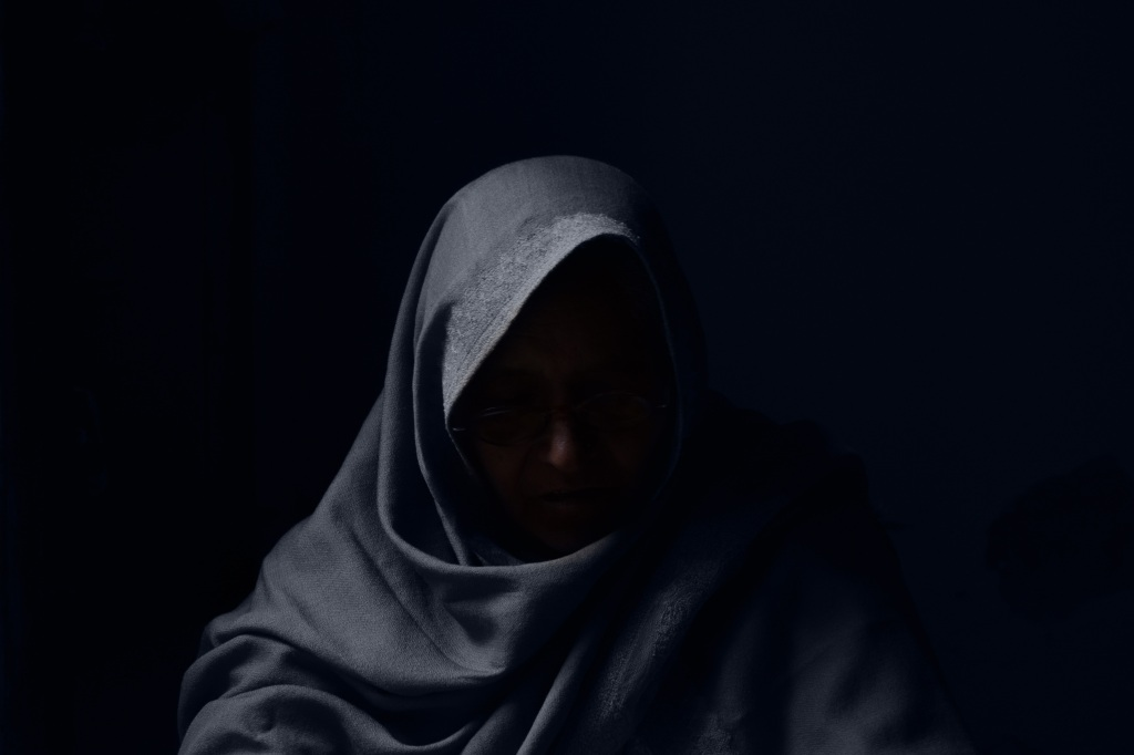 Hooded, cloaked figure with face in shadow. Photo by Ady on Unsplash